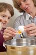 Mutter und Sohn beim Backen - Eier werden getrennt
