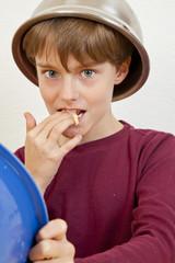 beim Backen - Junge mit Schüssel auf dem Kopf nascht Teig