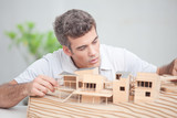 Architect working on a mock-up house poster
