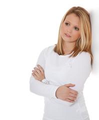 Junge Frau lehnt verträumt an weißer Wand