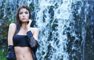 A young brunette model on a waterfall background