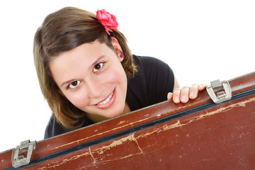 Beautiful young woman smiling from behind a suitcase