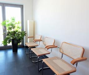 Drei Stühle mit Stehlampe und Pflanze vor weisser Wand