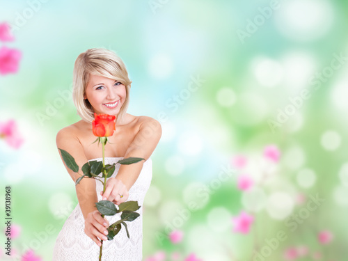 junge blonde Frau im weißen Kleid mit Rose
