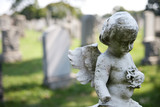 Angel with wings above headstones in cemetery poster