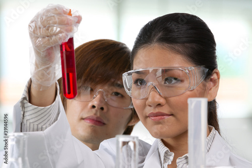 Two scientists analyzing solution.