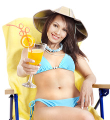 Girl in bikini drinking orange juice.