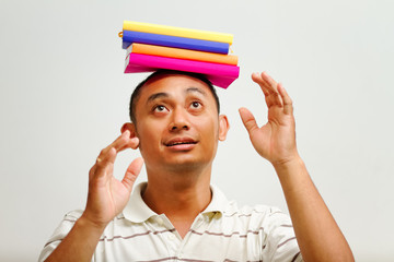 ethnic male student balancing books on head