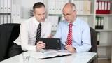 zwei geschäftsleute arbeiten mit tablet-pc im büro