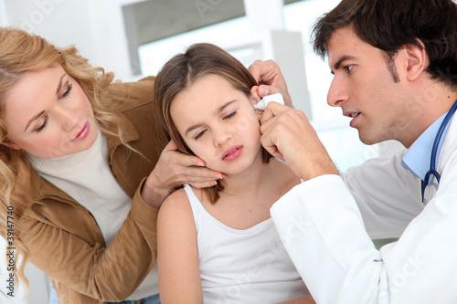 Leinwanddruck Bild Doctor looking at little girl ear infection