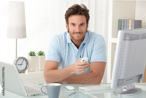 Smiling man at desk with mobile phone