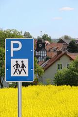 Wanderschild vor Rapsfeld und Dorf