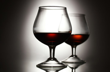 Two glasses of cognac on grey background