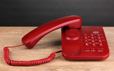 Red phone on wooden table on grey background