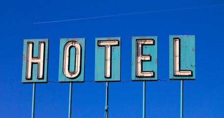 Grungy Old Hotel Sign And Airplane Isolated On Blue