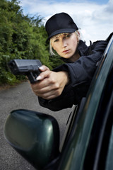 Young police woman holding a gun
