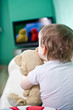 Child with teddy bear watching TV