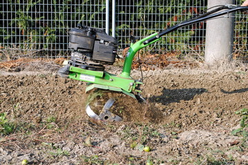 green rotary tiller working in the garden