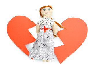 Voodoo doll girl on the broken heart isolated on white