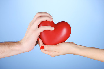 Man and woman holding red heart in hands on blue background