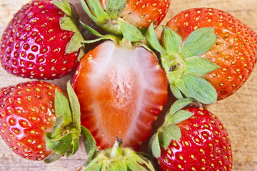 A group of whole, organic strawberries around a sliced strawberr