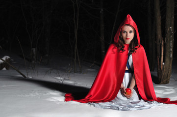 Red Riding Hood in the winter night forest
