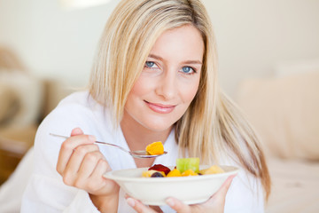 closeup of young attractive woman eating fruit salad on bed