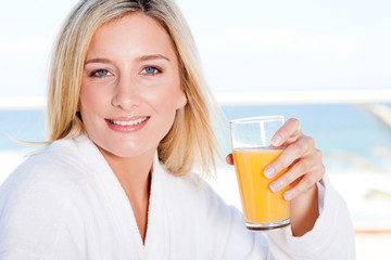 pretty young woman drinking orange juice in the morning