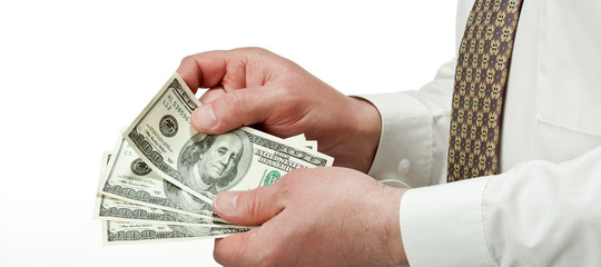 Businessman's hands counting dollar banknotes