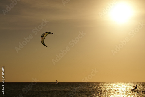 Kitesurfer's silhouette against the sun