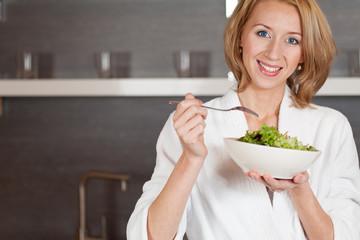 junge frau isst salat in der küche mit freude