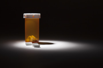 Medicine Bottle and Pills Under Spot Light