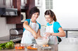 teen daughter helping mother baking in kitchen