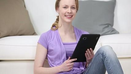 junge frau tippt auf ihrem tablet-pc im wohnzimmer