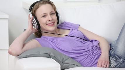 lächelnde frau liegt mit kopfhörer auf dem sofa