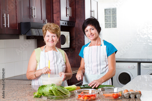 happy middle aged woman cooking with senior mother in kitchen