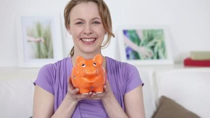 lachende junge frau mit ihrem sparschwein
