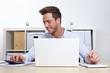 Mann am Laptop mit Taschenrechner