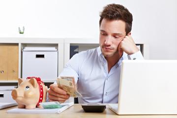 Mann mit Sparschwein und Geldscheinen