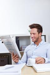 Mann im Büro liest Zeitung