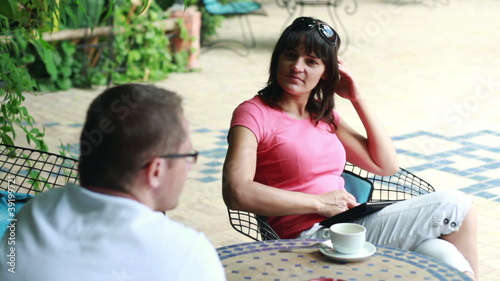 Happy young couple drinking coffee in bar, outdoors