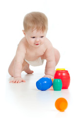 funny baby goes down on all fours with color toys