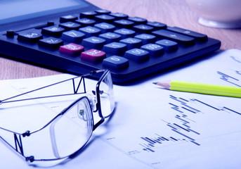 eyeglasses, calculator, pencil and diagram