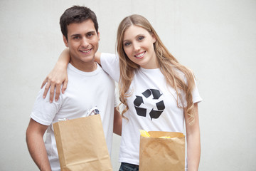 Couple holding paper garbage bags