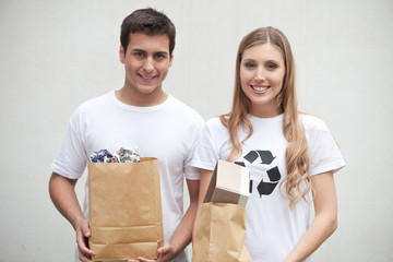 Couple holding garbage bags