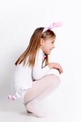 Mädchen hoppelt im Hasenkostüm