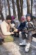 Tata pomaga dzieciom założyć łyżwy