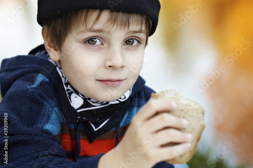 Little boy eating slice of bread Poster