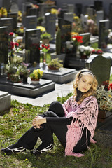 Young woman sitting at the cemetary