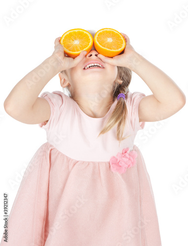 Little girl playing with fresh oranges over white